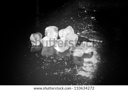 black and white ice cubes on an iced water surface - stock photo