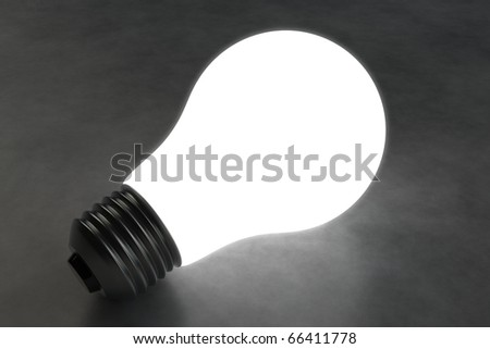 Black and white illuminated light bulb alone on a dark tile floor.