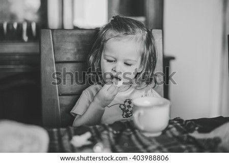 black and white image of a cute little girl sitting at a dining room table eating by herself - stock photo
