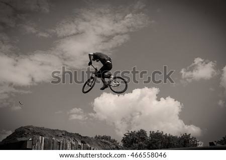 Black and white image of a cyclist on the background of sky and clouds