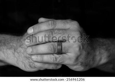 Black and white image of a detail of a man's hands folded on top of each other
