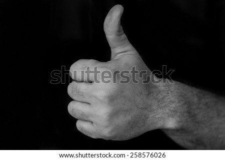 Black and white image of a hand giving a thumbs up - stock photo