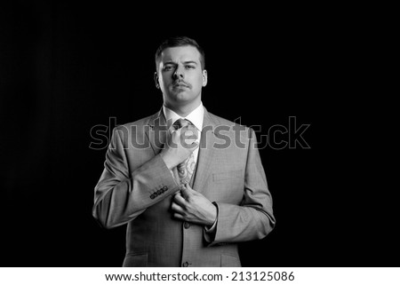 Black and white image of a man in a suit over a black background