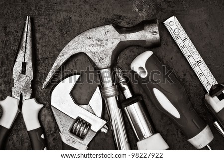 Black and white image of a set of tools on a textured metallic background - stock photo