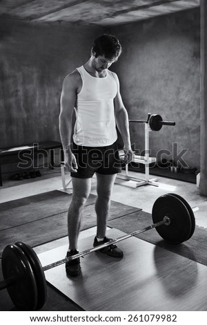 Black and white image of a strong young man looking quietly at the weights he is about to lift