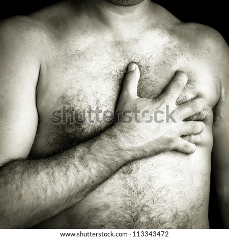 Black and white image of a topless man suffering a pain in his chest - stock photo