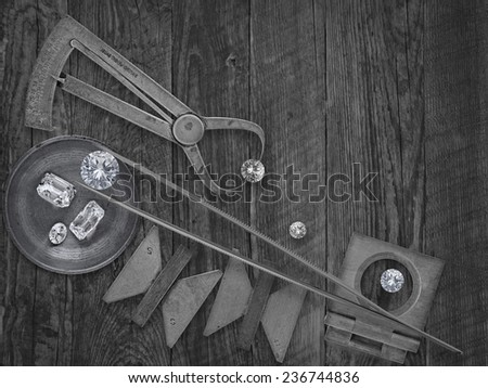 black and white image of a vintage jeweler tools and diamonds over wooden bench, space for text - stock photo