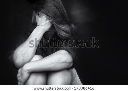 Black and white image of a young woman crying and covering her face useful to illustrate stress, depression or domestic violence - stock photo