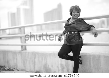 Black and white image of a young woman leaning on a guard rail - stock photo