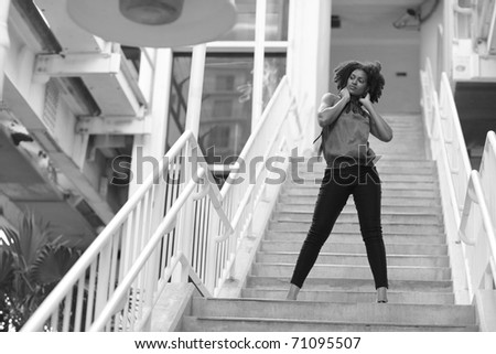 Black and white image of a young woman posing on a staircase - stock photo