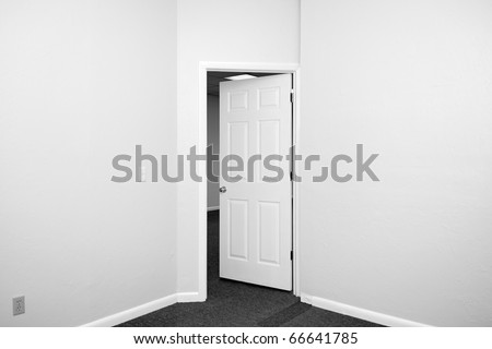 black and white image of an empty room with door opening out