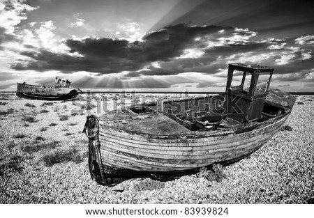black and white image of an old wooden fishing boats left to rot and decay on the shingle beach at Dungeness, England, UK.