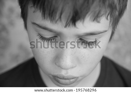 Black and white image of boy looking sad, looking down - stock photo