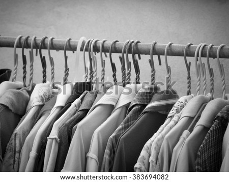 Black and white image of clothes hanging on hanger rack. Choice of fashion clothes on hangers. - stock photo