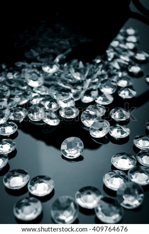 Black and white image of diamonds scattered on a shiny surface