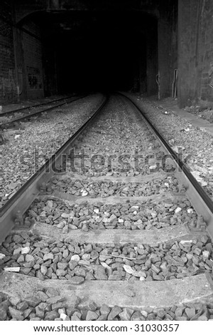 Black and white image of railway on the entrance of tunnel - stock photo