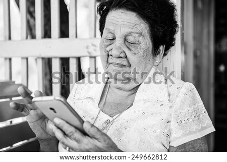 Black and white image of Senior asian woman  with smart phone - stock photo