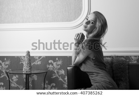 black and white image of sophisticated female is sitting on sofa in elegant ambient near fur with shiny blue dress and long hair. She is looking in camera and smiling  - stock photo