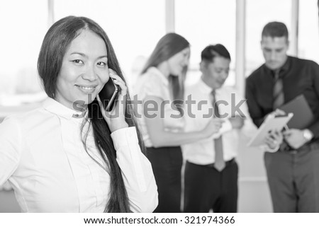 Black and white image of successful asian business woman with magnificent long hair using mobile phone and business team at background. - stock photo