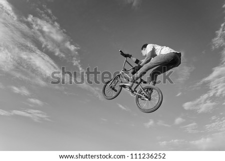 Black and white image of teenager on a bicycle in a jump on a background blue sky. - stock photo
