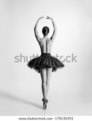Black and white image of the back view of a young, beautiful, topless ballet dancer with a light background - stock photo