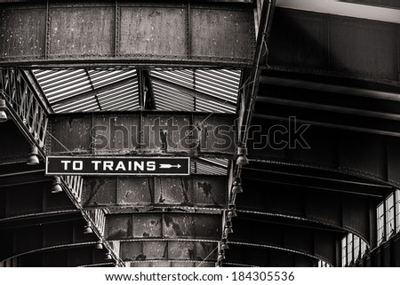 Black and white image of the signs inside an abandoned train station showing the rust and corrosion - stock photo