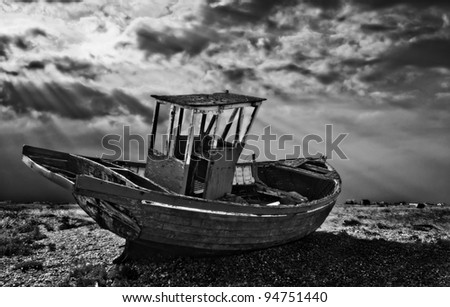 black and white image of the surreal landscape of dungeness in south east england. Abandoned fishing boats litter the shingle beach just rotting away. - stock photo