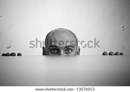 Black and white image of top of man's face looking stressed; caucasian/white, 31-45 years of age, bald - stock photo
