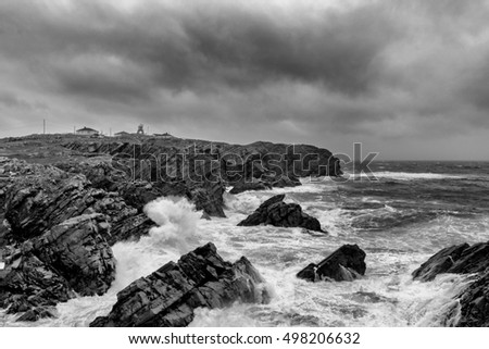 Black and white image of waves crashing on shoreline of Bonavista Newfoundland with lighthouse in the background