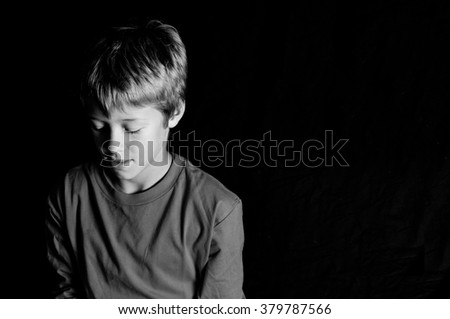 Black and white indoor studio portrait of young boy looking down with copyspace. - stock photo