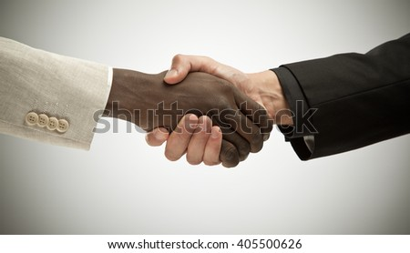 black and white interracial handshake isolated on grey - stock photo