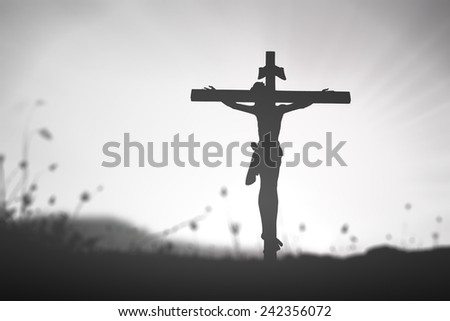 Black and white Jesus with the cross on blurred sunset background. - stock photo