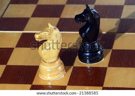 black and white knights on a chessboard - stock photo