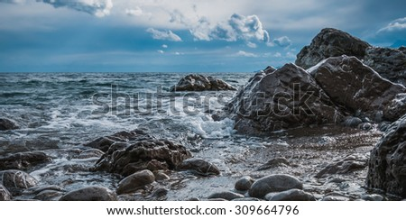 black-and-white landscape waves of sea with a rocky coastline