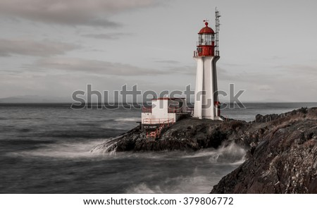 Black and white long exposure with contrasting red features of Shearingham lighthouse on Vancouver Island British Columbia, Canada. - stock photo