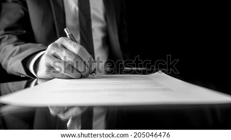 Black and white low angle image of the hand of a businessman in a suit signing a document or contract with a fountain pen on a reflective surface. - stock photo