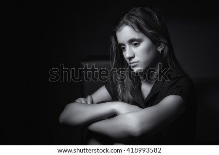 Black and white low key portrait of a sad teenage girl with a thoughtful and worried expression