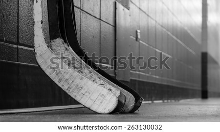 Black and white macro shot of hockey stick blades laid on a dirty arena floor - Shallow depth of field - stock photo