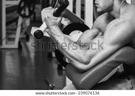 Black and white man in the gym. Working out with weights.Man makes exercises. Sport, power, dumbbells, tension, exercise - the concept of a healthy lifestyle. Article about fitness and sports. - stock photo