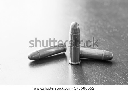 Black and white, 9mm bullets on table - stock photo