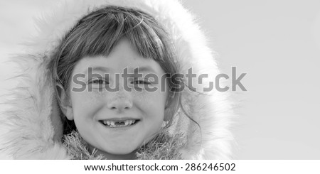 black and white monochromatic image of six year-old red haired girl with two front teeth missing and wearing Eskimo style fur lined hood - stock photo