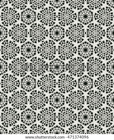 Black and white monochrome seamless pattern background made of repeating scanned elements of handmade crochet lace