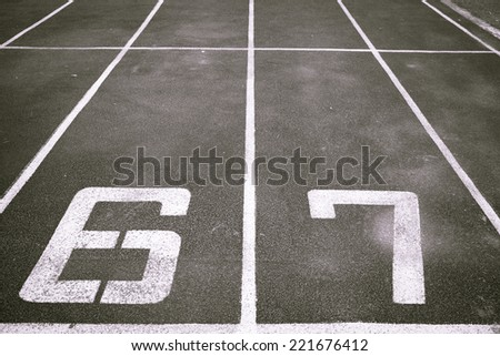 black and white number six and seven on running track rubber  - stock photo