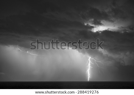 Black and white of a lightning bold striking the surface of the ocean during a thunder storm.  - stock photo