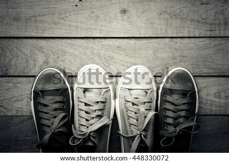 Black and white of canvas shoes with copy space on wooden board, flat lay, top view background