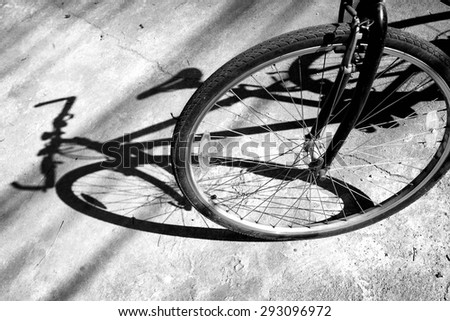 Black and white of Front wheel of a bicycle against shadow / Front wheel of a bicycle - stock photo