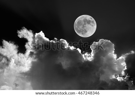 Black and white of full moon in night sky with dreamy moonlit clouds
