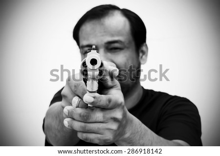 black and white of man holding gun and pointing his gun revolver. Selectively concentrated on the front of the gun. - stock photo