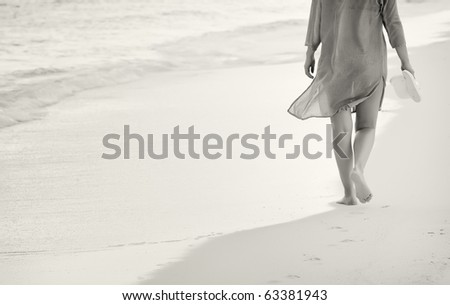 Black and white of young woman walking on the sand - stock photo