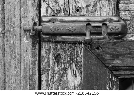 Black and white old door with rusty latch - stock photo
